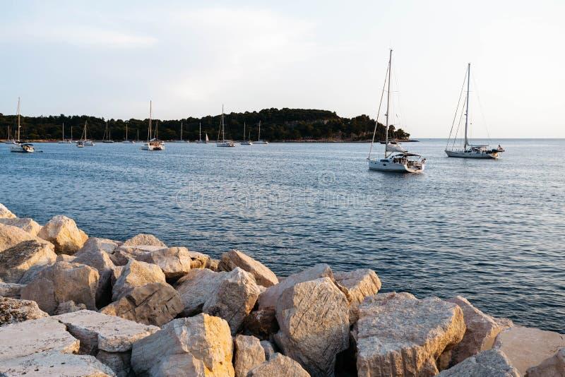 Stenpir på solnedgången I havssegelbåten med en mast och segla Mot bakgrunden av en ö arkivfoton