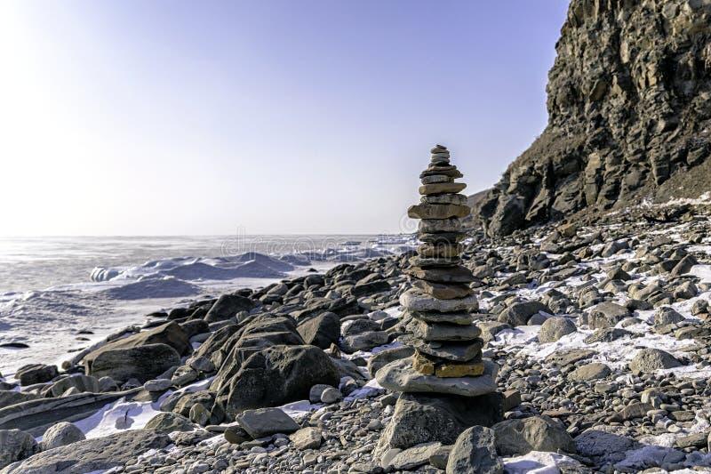 Stenpyramid i vinter på en stenig strand av den djupfrysta fjärden som täckas med snö royaltyfri bild