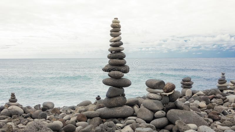 Stenpyramid på kiselstenhavstranden som symboliserar stabilitet, zen, harmoni, jämvikt royaltyfri bild