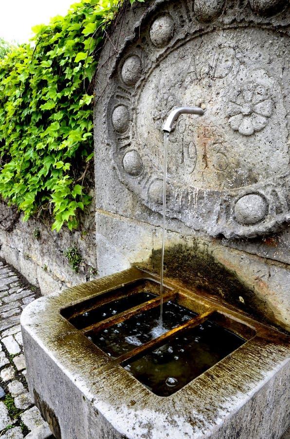 Stenspringbrunn och stenlagd väg royaltyfri foto