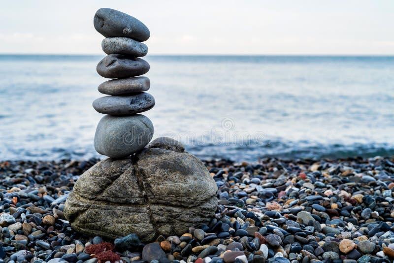 Stentorn av kiselstenar på havskust arkivfoton