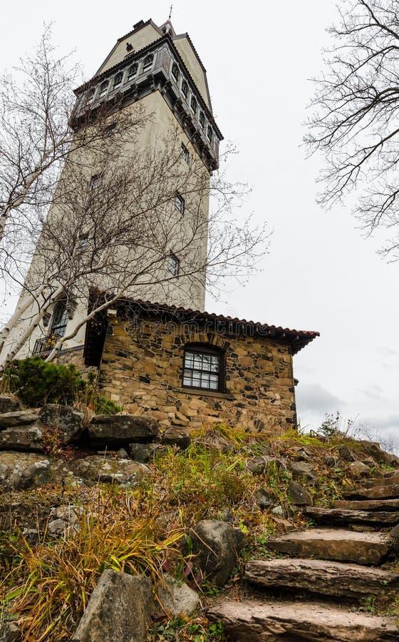 Stentrappan leder till stugan med tornet på mörk molnig dag royaltyfri foto