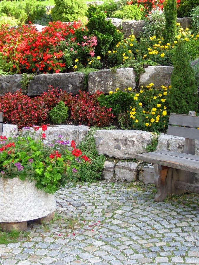 Stenvägg, bänk och växter på färgrik landskap trädgård. arkivbilder