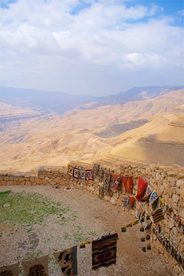 Stenvägg i öken med flaggor och matta royaltyfria foton
