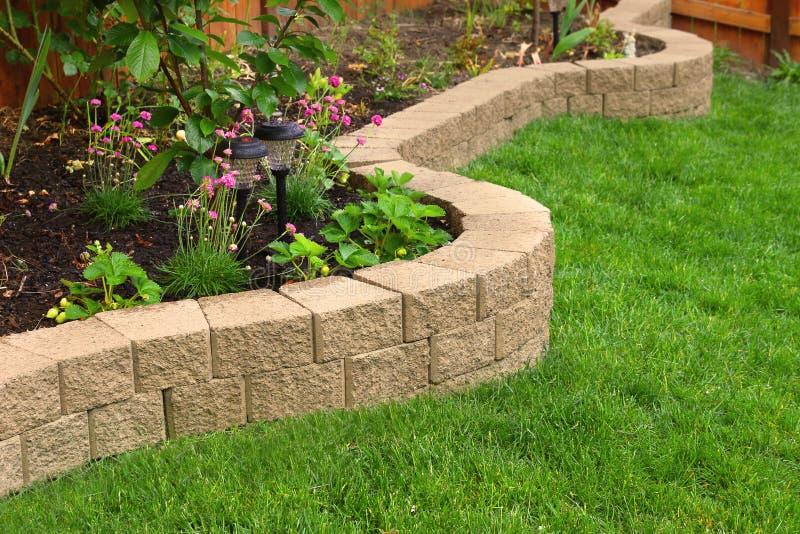 Stenvägg med perfekt gräs som landskap i trädgård med konstgjort gräs royaltyfri fotografi