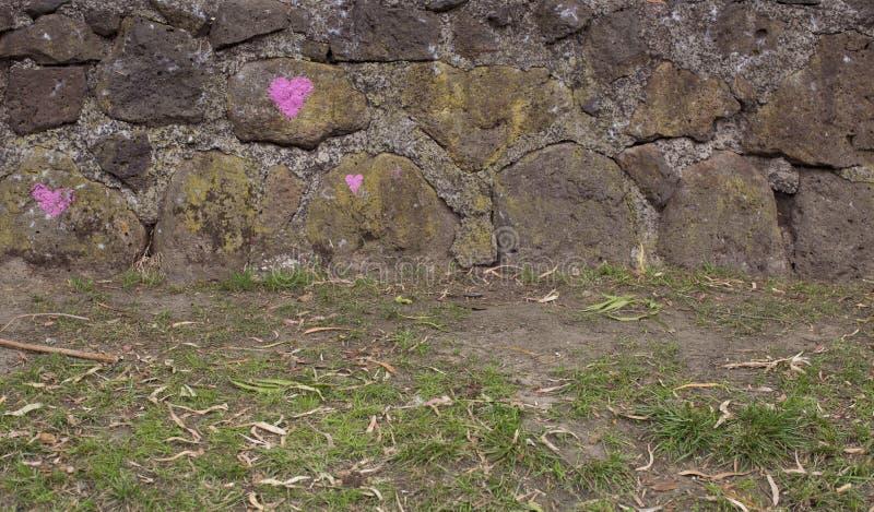 Stenvägg med tre rosa hjärtor royaltyfri bild