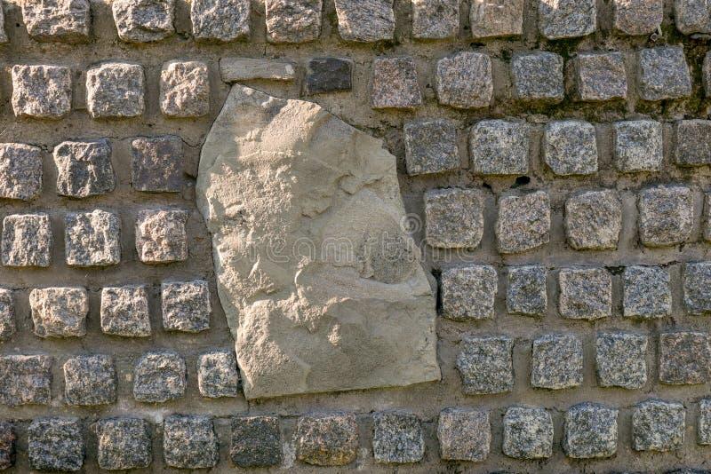 Stenvägg som dekoreras med granitstenar med en stor sten i mitten royaltyfria foton