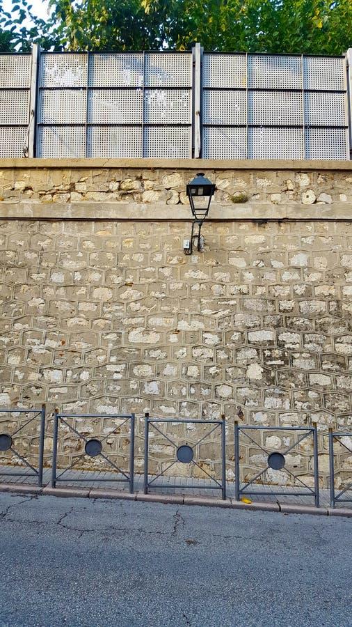 Stenvägg vid en väg med räcke och gröna växter royaltyfria bilder