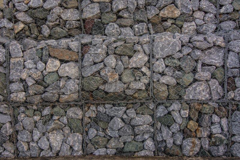 Stenväggar i netto förhindrar jord och stenar glidbanor arkivbilder