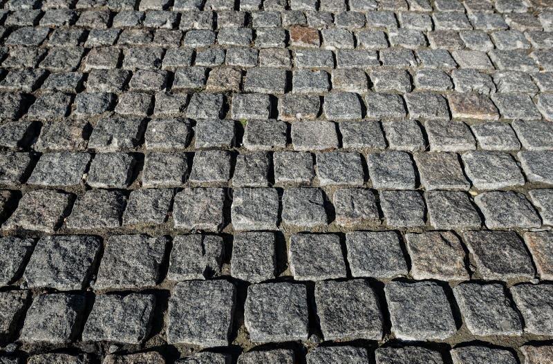 Stenvägslut upp Gammal trottoar av granit Grå kullerstentrottoar Övre åtlöje eller tappninggrungetextur arkivbild