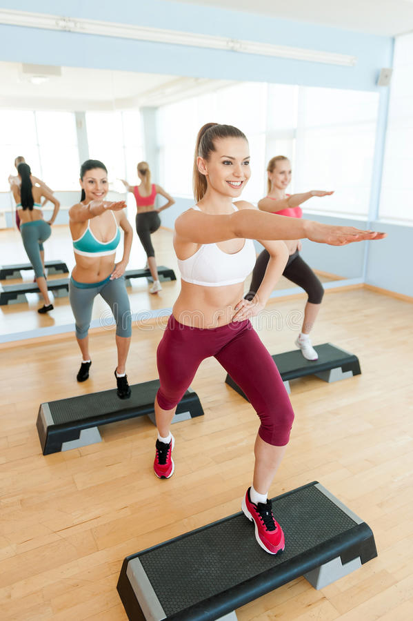 Step aerobics. Top view of three attractive young women in sports clothing doing step aerobics together and smiling royalty free stock photography