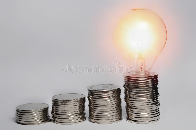 Step of coin stack with light bulb royalty free stock photography