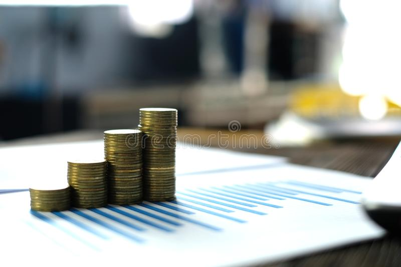 Step of coins stacks with notebook laptop computer and financial graph on white paper on working table, business planning vision. And finance analysis concept stock photo