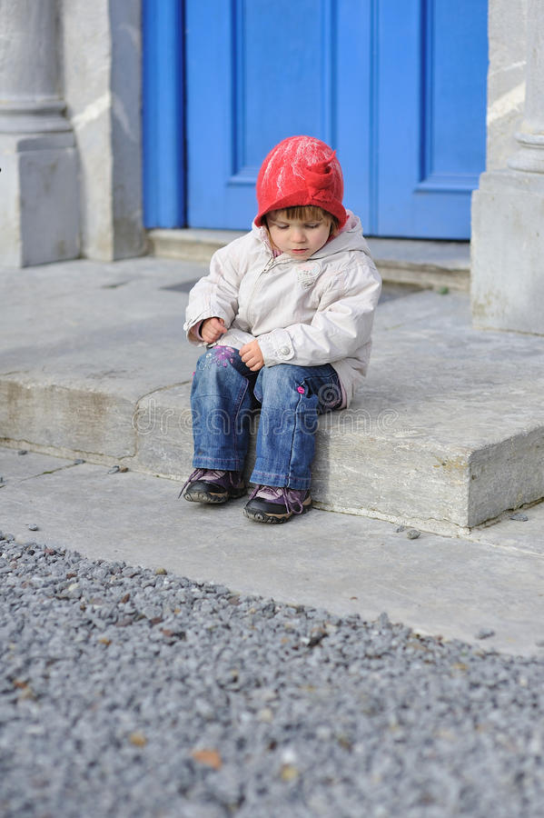On a Step. A little girl sitting on a step royalty free stock photos