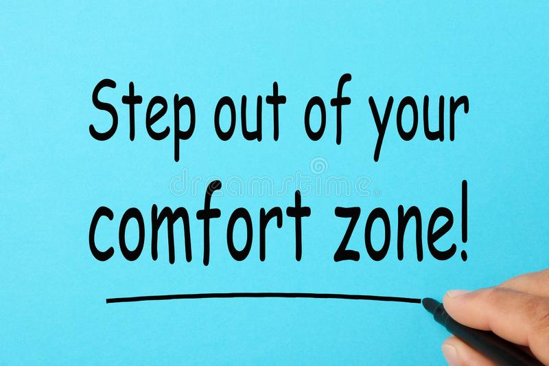 Step Out of Your Comfort Zone. Handwriting `Step out of your comfort zone!` on a blue background. Business Concept stock photos