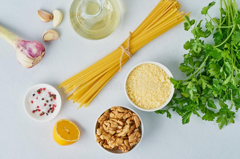 Step by step recipe. Pesto pasta, bavette with walnuts, parsley, garlic, nuts, olive oil. Top view, blue background royalty free stock photography