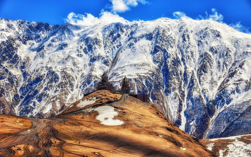 Caucasus mountains, ancient Gergeti Trinity church Tsminda Sameba against the glacier near mount Kazbek, landmark of Georgia. Stepansminda, Georgia - April 15 stock images