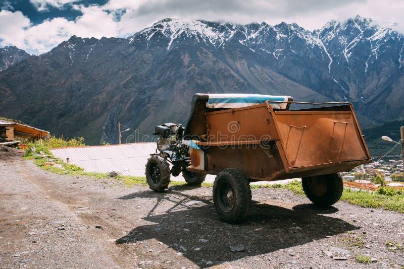 Stepantsminda Gergeti, Georgia Liten gammal Två-hjul traktor med royaltyfri foto