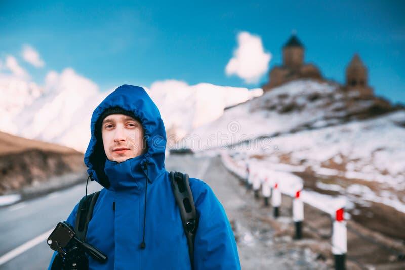 Stepantsminda, Gergeti, Gruzja Mężczyzny Backpacker podróżnika Turystyczny fotograf Pozuje Blisko Świętej trójcy kościół - Tsmind obraz stock