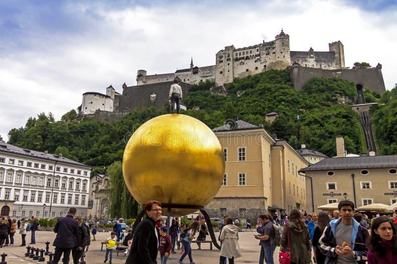 Stephan Balkenhol - Sphaera, een beeldhouwwerk van een mens op een gouden gebied op KapitelplatzChaptr-vierkant in Salzburg, Oost stock foto's