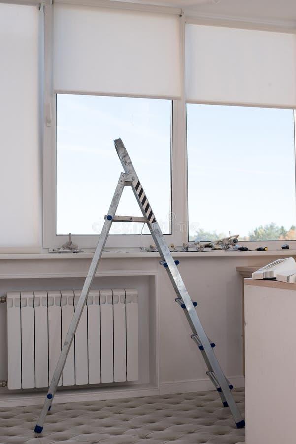 Stepladder schodki w mieszkaniu okno przeciw tłu remontowi materiały zdjęcie stock