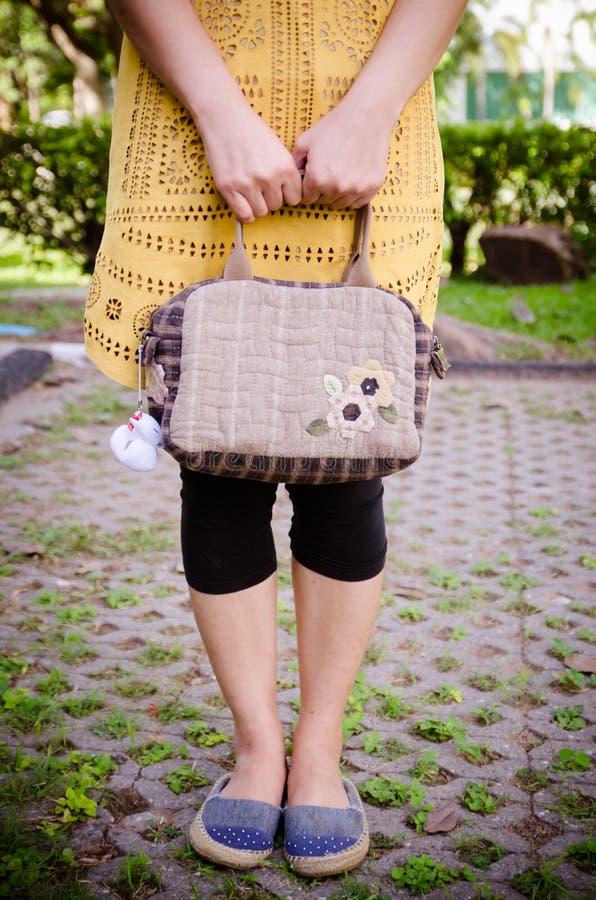 Steppende Tasche in den Händen von Frauen stockfoto