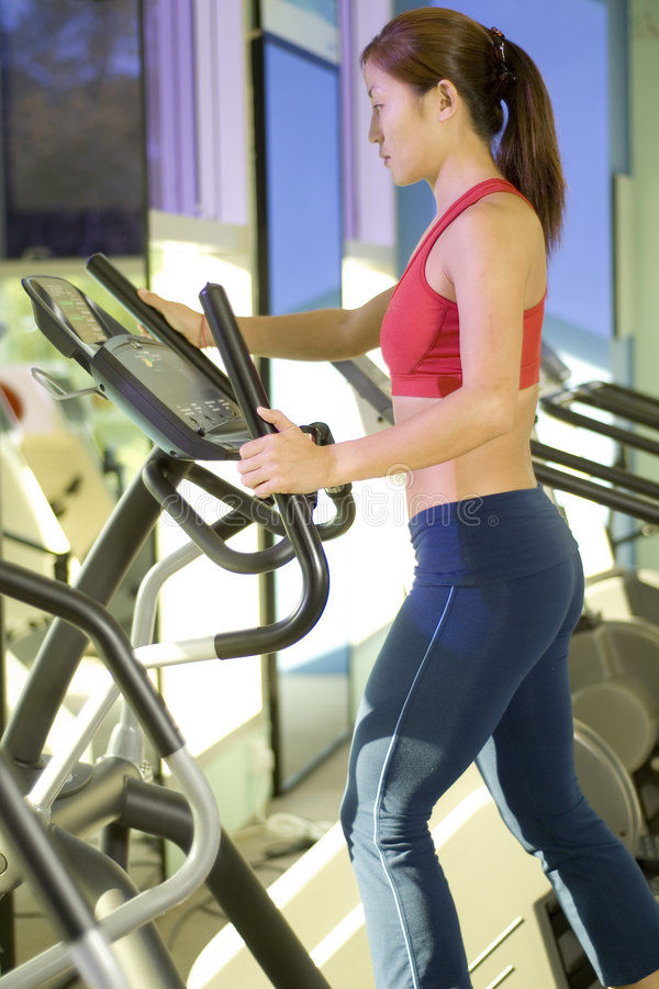 Stepper. A woman does some cardio exercise on a step machine