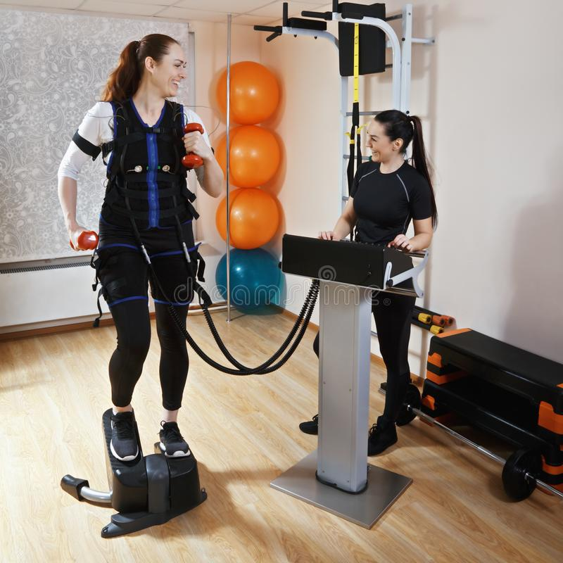 Stepper training. Caucasian women training on stepper with weights in gym. Female trainer standing aside manages electric muscle stimulation purposed to increase stock photos