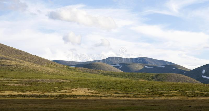 Steppes of the northern Taiga. The grassy steppes of the northern Taiga in Mongolia, home of the Tsaatan reindeer herders, with summer snow in the north facing royalty free stock photos