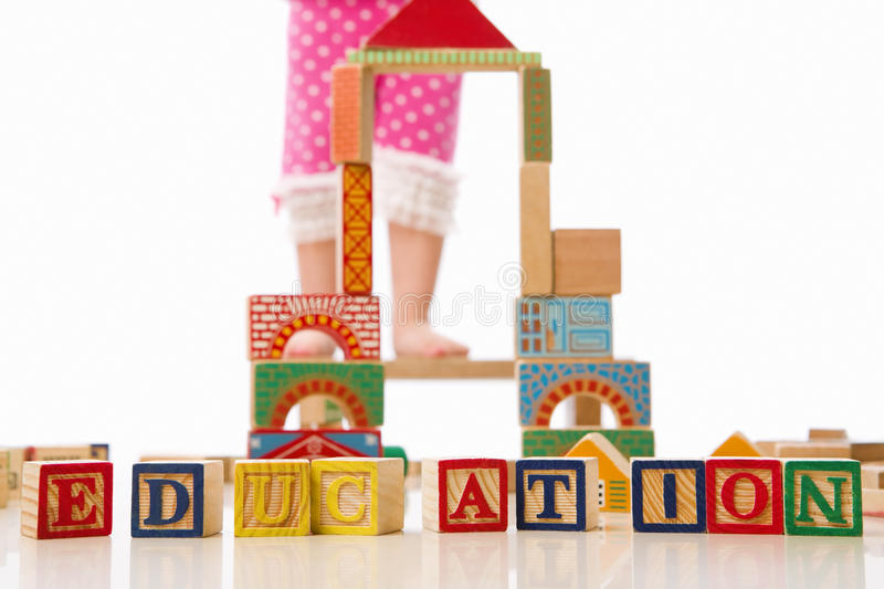 Stepping higher on education. Concept with little kid standing on short wooden chair with education word in front of it. *** Main focus on EDUCATION word block stock images