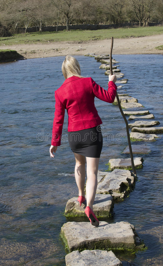 Stepping stones woman walking across river royalty free stock image
