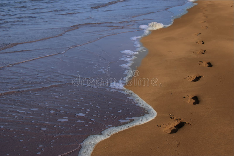Steps 1. Footprints left in the sand of an irish beach with the tide coming in stock image