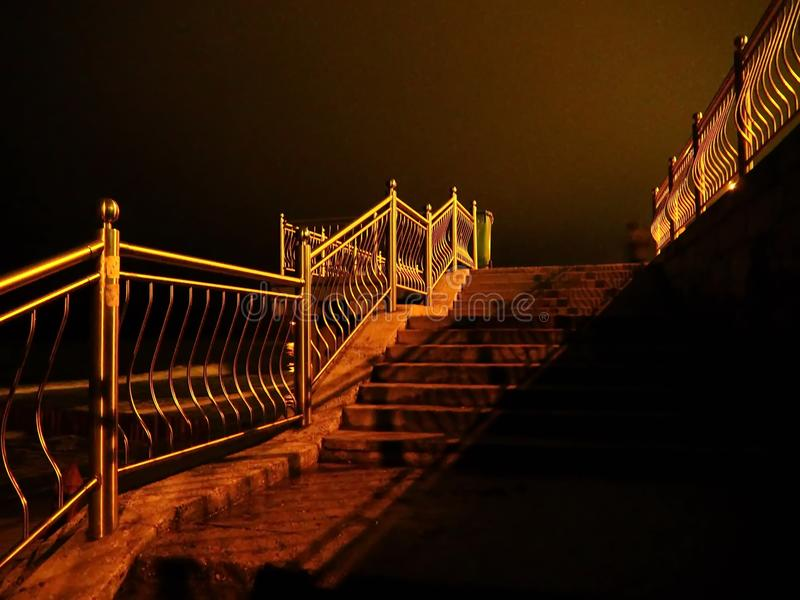 Night Golden staircase railing support from darkness to light. The steps of the brightens up the warm evening wandering the beautifully philosophical mood to stock photos