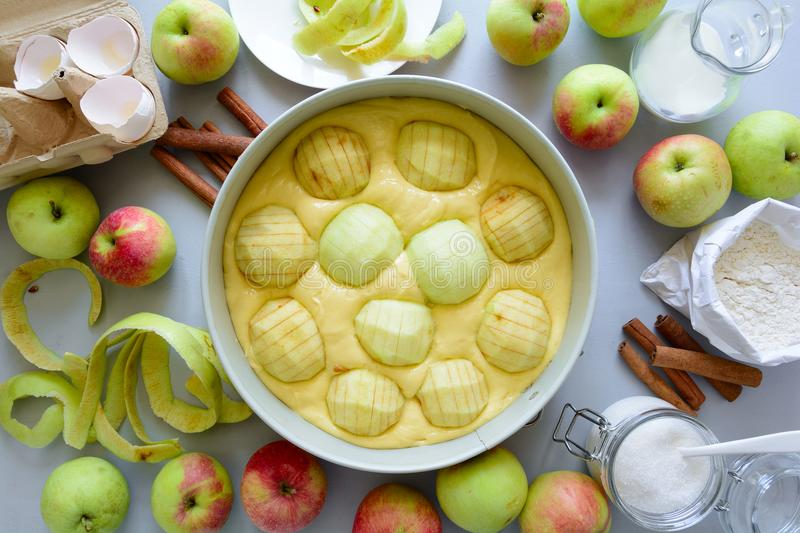 Steps of cooking apple pie. Fresh harvest apples, cinnamon, flour, sugar, butter, eggs, milk and baking mold. On gray wooden background. Top view. Flat lay stock photography
