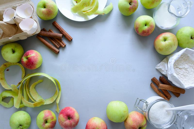 Steps of cooking apple pie. Fresh harvest apples, cinnamon, flour, sugar, butter, eggs, milk and baking mold. On gray wooden background. Top view. Flat lay royalty free stock photo