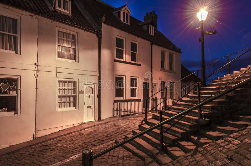 Steps and cottages illuminated by a street lamp at dusk. stock images