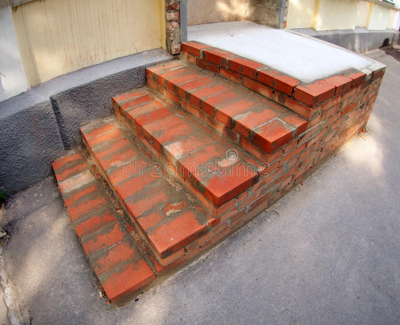 Steps of the porch outside the house under construction. The steps of the porch outside the house of red brick under construction with wide angle distortion view royalty free stock photos