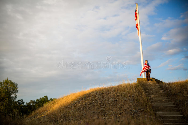 Steps to freedom. A young boy with an American Flag, joy of being an American royalty free stock image