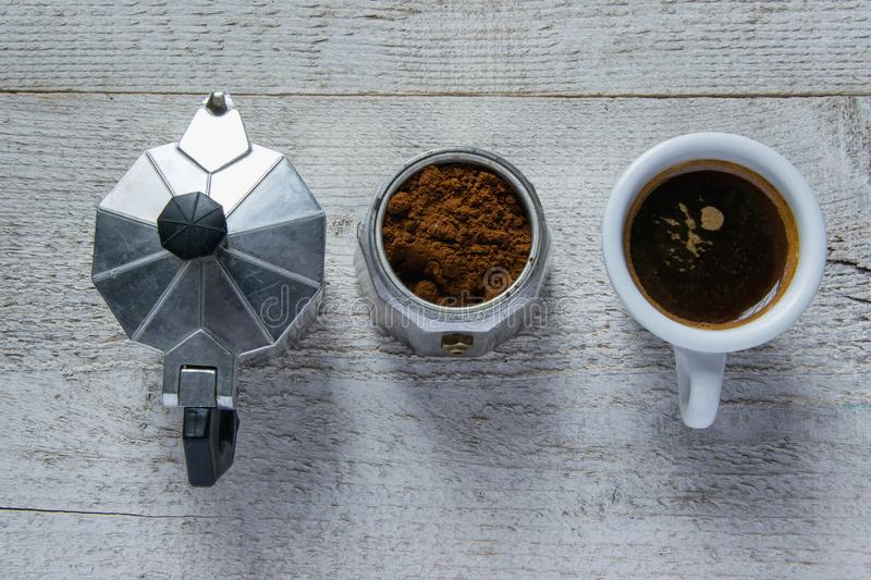 Top view of moka - italian coffee maker and coffee cup on wooden white background. The steps to make the cafe. Top view of moka - italian coffee maker and coffee stock photos