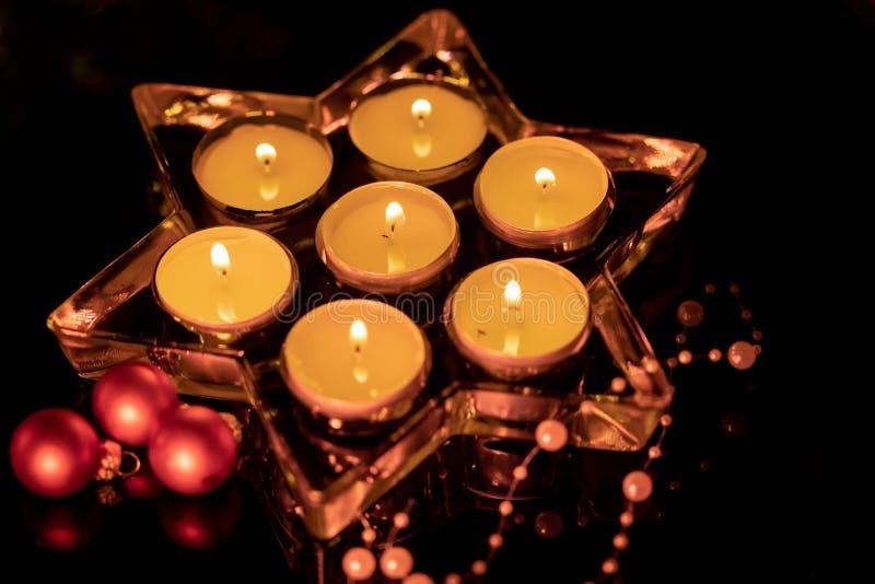 Ster die van glas zeven brandende kaarsen bevatten stock afbeeldingen