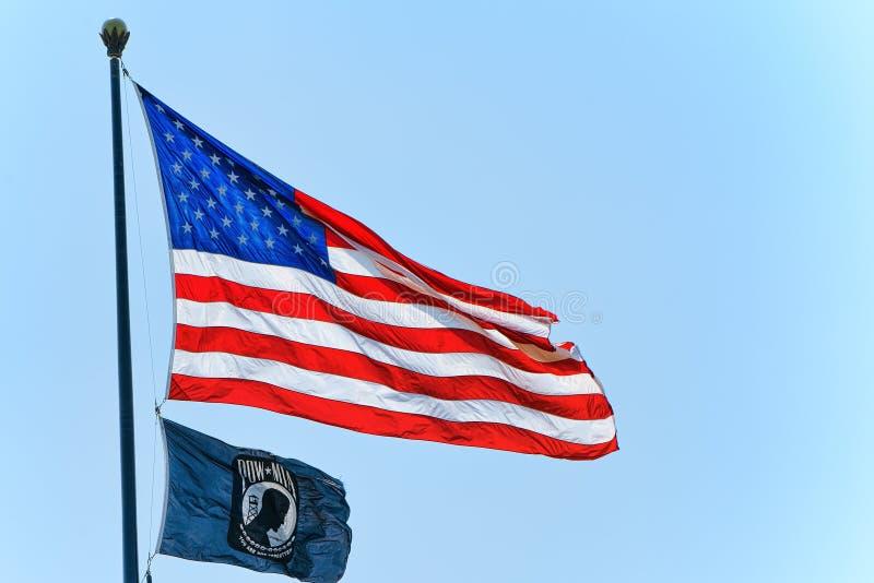 Ster-gestreepte Amerikaanse vlagopwinding trots tegen de blauwe hemel stock fotografie