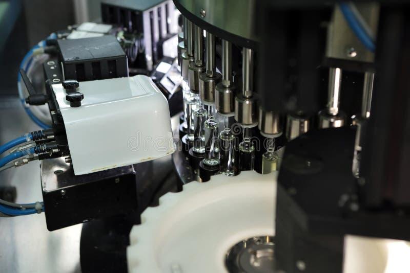 Sterila kapslar för injektion Flaskor på den buteljera linjen av den farmaceutiska växten Maskin, når att ha kontrollerat sterila arkivbild