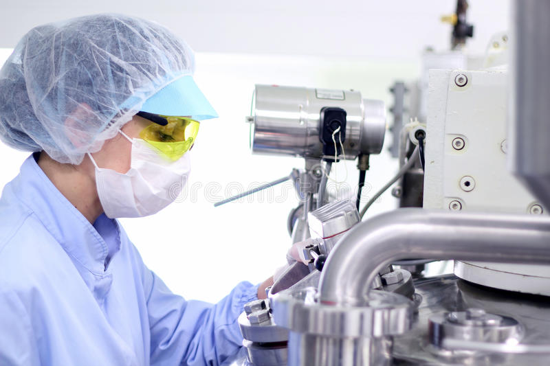 Sterile Environment - Pharmaceutical Factory. Pharmaceutical technician works in sterile working conditions at pharmaceutical factory royalty free stock image
