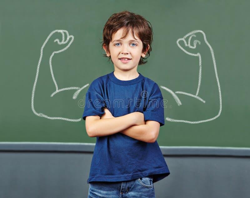 Sterk kind met spieren in school stock foto's