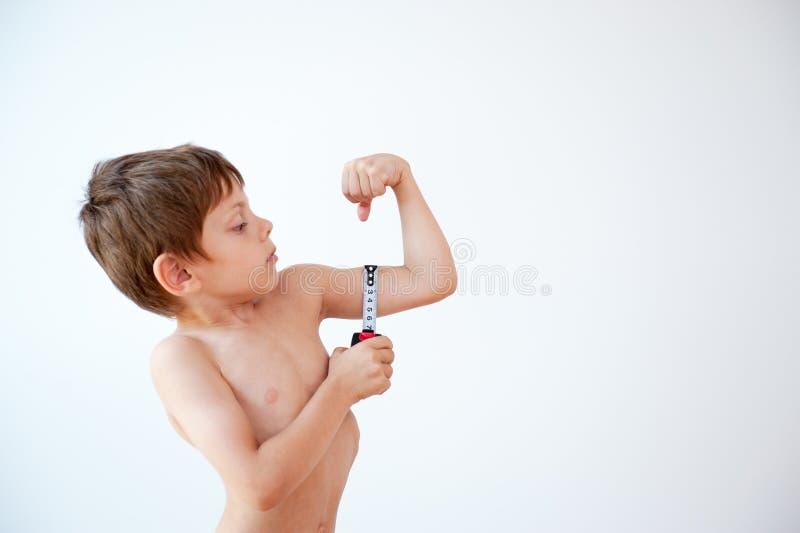 Sterk meet weinig jongen zijn spieren met een metende band met exemplaar ruimteachtergrond royalty-vrije stock afbeeldingen