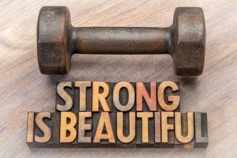 Sterk is mooi - woordsamenvatting in uitstekend houten type stock foto