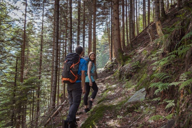 Sterk paar die in de bergen wandelen stock foto's