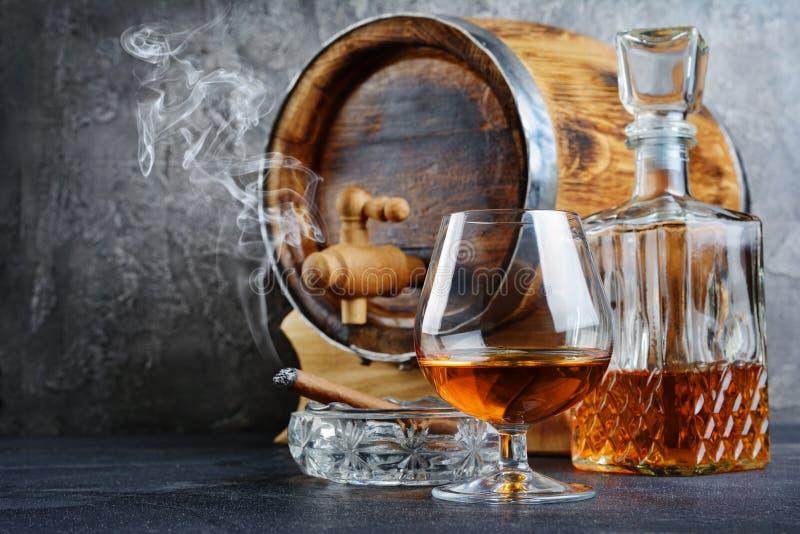 Sterke alcoholisch drinkt cognac in snifferglas met rokende sigaar in asbakje, kristalkaraf en uitstekend houten vat stock fotografie