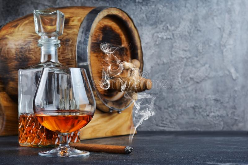 Sterke alcoholisch drinkt cognac in snifferglas met rokende sigaar, kristalkaraf en uitstekend houten vat in kelder stock fotografie