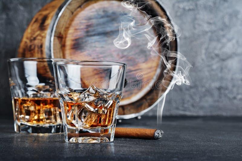 Sterke alcoholische drank Schotse wisky met ijsblokjes in oude manierglazen met rokende sigaar en uitstekend houten vat in kelder royalty-vrije stock afbeelding
